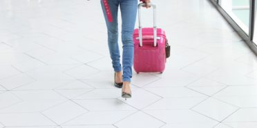 Woman's lower half walking wheeling baggage behind her